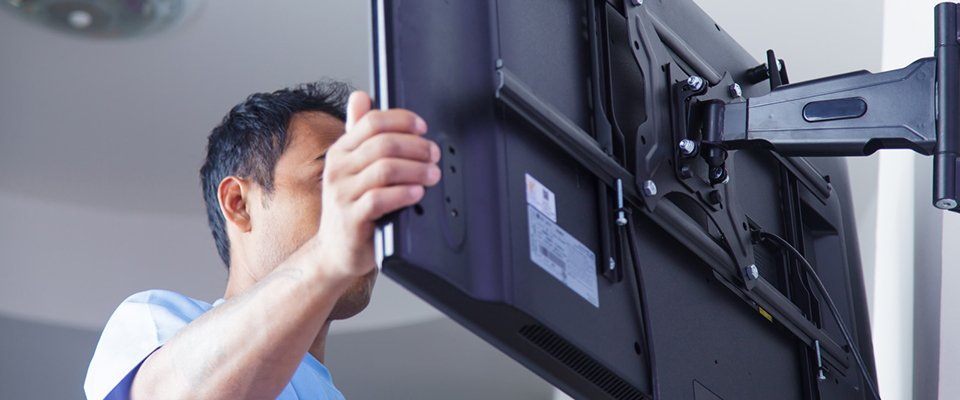 Man mounting flat screen TV