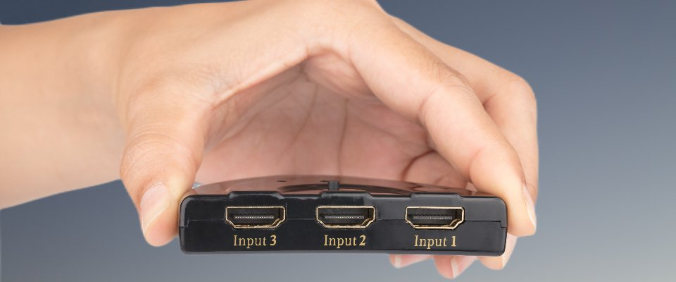 Hdmi Switch Explained: Man Holding An Hdmi Switcher