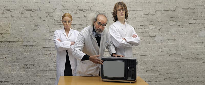 Three scientists with an old TV
